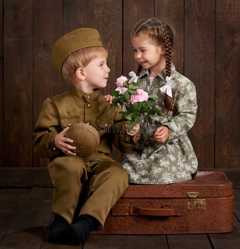 Le garçon d'enfants sont habillés comme soldat dans de rétros uniformes militaires et fille dans la robe rose se reposant sur la  photo stock