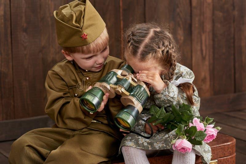 Le garçon d'enfants sont habillés comme soldat dans de rétros uniformes militaires et fille dans la robe rose se reposant sur la  photographie stock libre de droits
