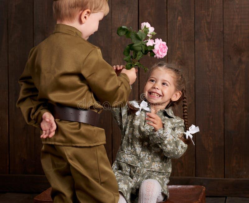 Le garçon d'enfants sont habillés comme soldat dans de rétros uniformes militaires et fille dans la robe rose se reposant sur la  photos stock
