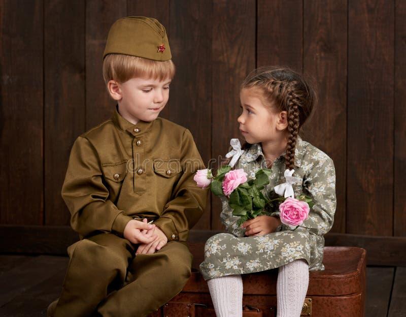 Le garçon d'enfants sont habillés comme soldat dans de rétros uniformes militaires et fille dans la robe rose se reposant sur la  photos libres de droits