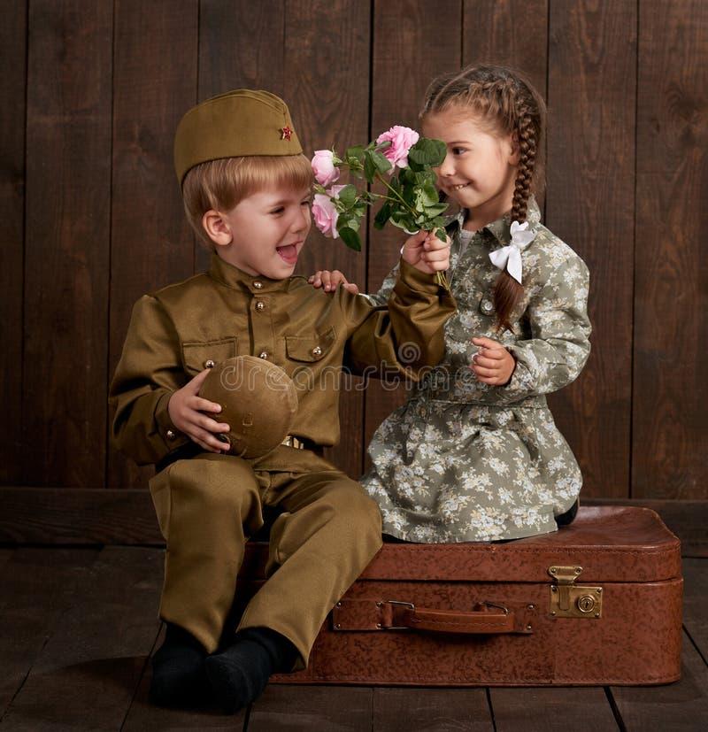 Le garçon d'enfants sont habillés comme soldat dans de rétros uniformes militaires et fille dans la robe rose se reposant sur la  photographie stock