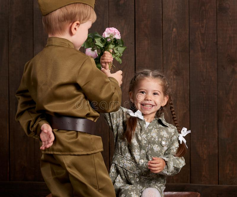 Le garçon d'enfants sont habillés comme soldat dans de rétros uniformes militaires et fille dans la robe rose se reposant sur la  image stock