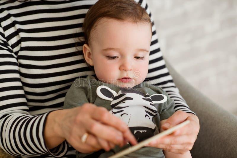 Le garçon d'un an s'assied face à un adulte sur un sofa gris photo stock