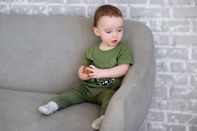 Le garçon d'un an s'assied sur un sofa gris et des sourires heureusement photo libre de droits