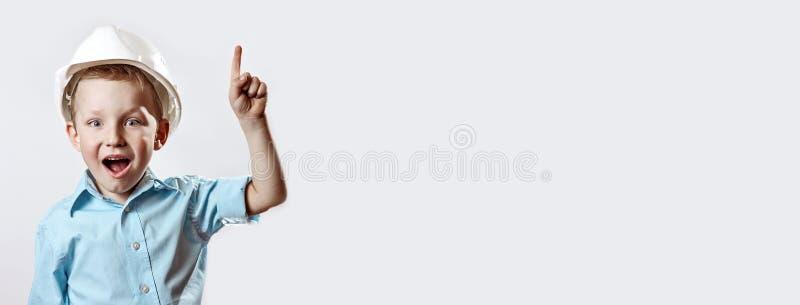 Le garçon dans le casque bleu-clair de chemise et de construction de l'agent de maîtrise a soulevé un doigt, comme si il avait tr images stock