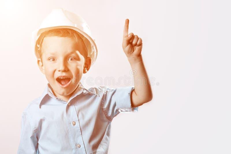 Le garçon dans le casque bleu-clair de chemise et de construction de l'agent de maîtrise a soulevé un doigt, comme si il avait tr photos libres de droits