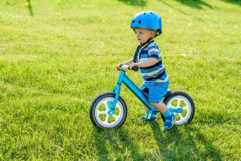 Le garçon dans le casque montant un vélo bleu d'équilibre courent le vélo images stock