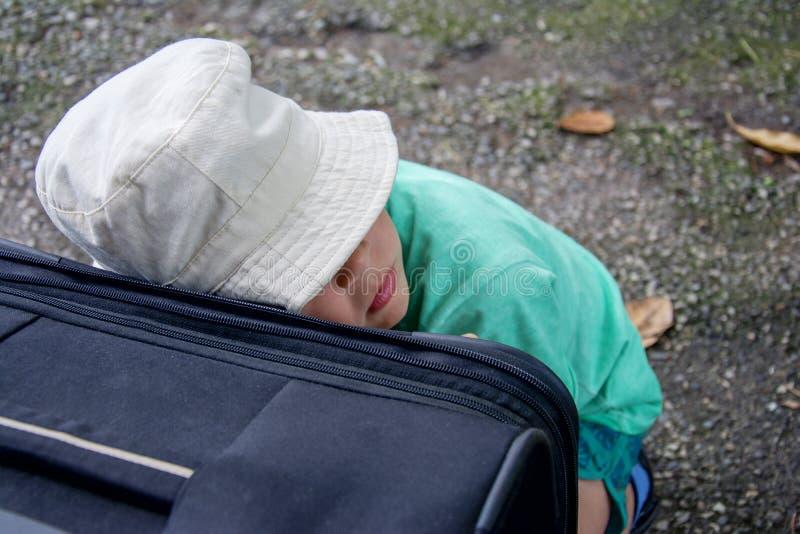 Le garçon dans le chapeau dort et s'est penché contre la valise attendant le train sur le voyage photographie stock libre de droits