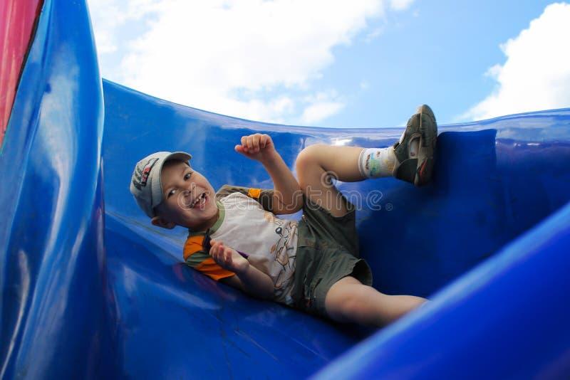 Le garçon dans le chapeau glissant sur la glissière bleue du ` s d'enfants photos stock