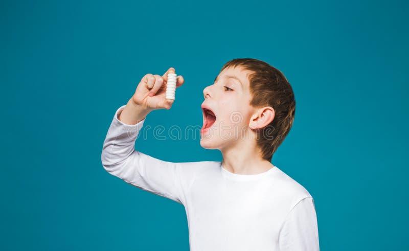 Le garçon dans des vêtements blancs essayent de manger beaucoup de pilules photographie stock libre de droits