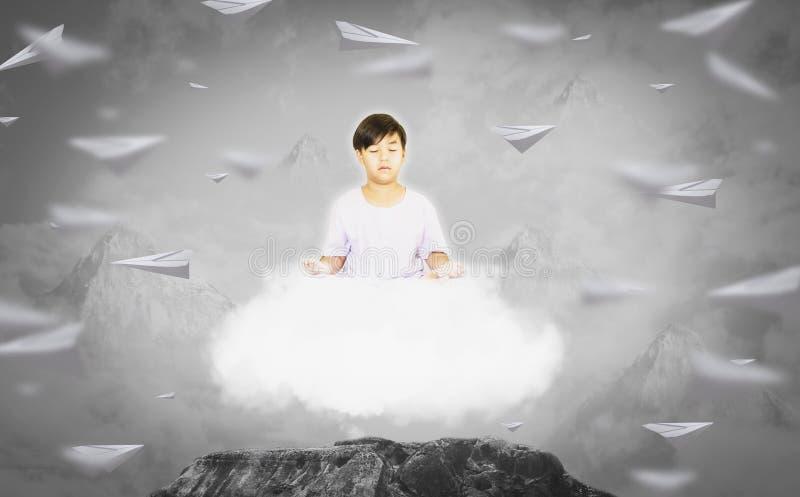 Le garçon dans des vêtements blancs, se reposant dans la méditation avec l'esprit pur, sur les nuages calmes flottant, fond est m photo libre de droits