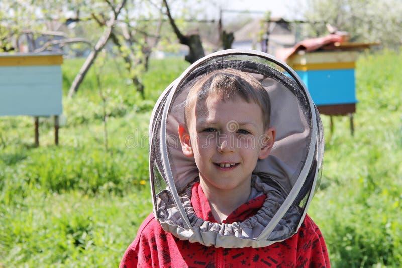 Le garçon dans l'apiculteur de vêtements de protection travaille à un rucher Apiculture photo libre de droits