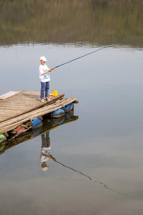 Le garçon dans la chemise blanche et le chapeau se tenant sur Pier With en bois Rod And Patiently Waiting To de pêche pêchent un  image libre de droits