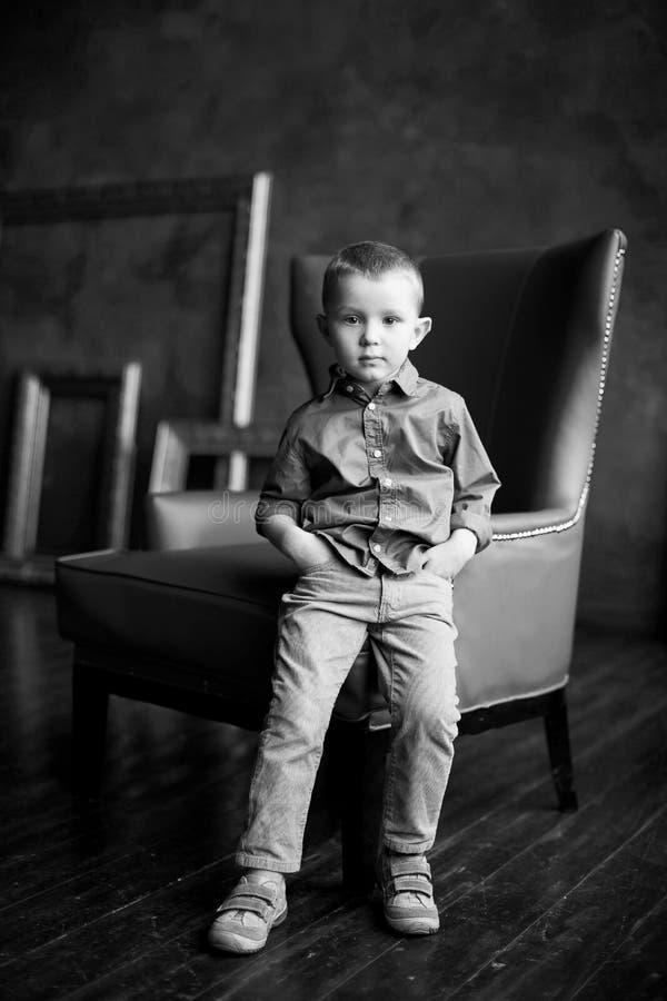 Le garçon dans la chemise et le velours côtelé bleus halète photos libres de droits
