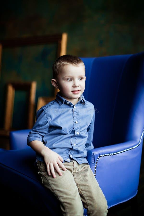 Le garçon dans la chemise et le velours côtelé bleus halète image libre de droits