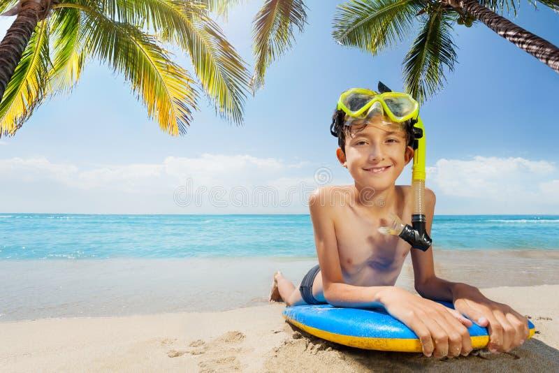 Le garçon dans le masque de scaphandre s'étendent sous le palmier sur la planche de surf image libre de droits
