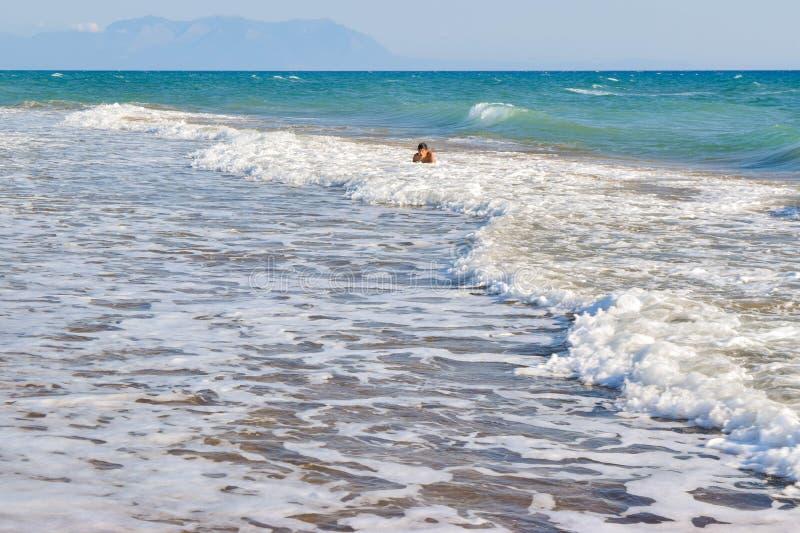 Le garçon dans le ressac de vague de mer photographie stock libre de droits