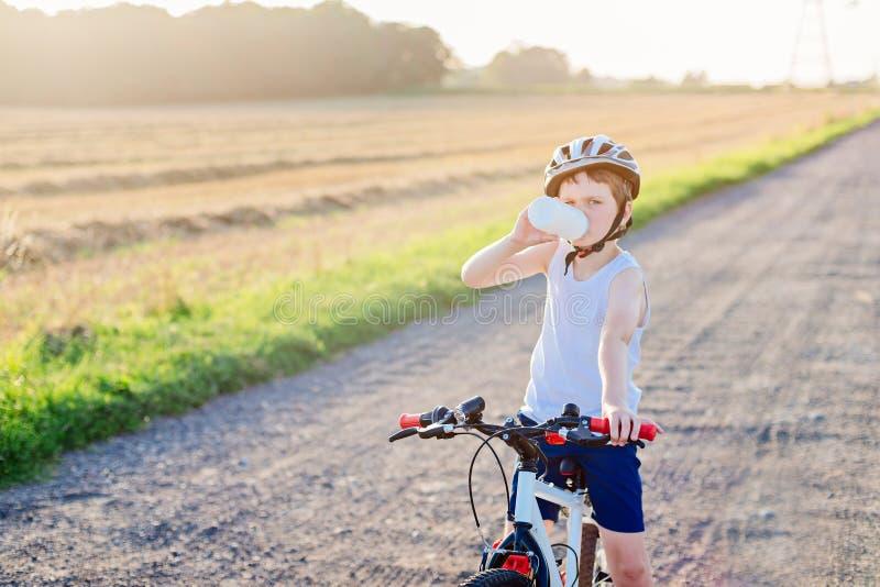 Le garçon dans un casque de bicyclette boit l'eau en bouteille photographie stock
