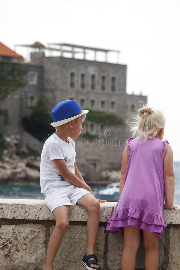 le garçon dans un chapeau bleu s'assied avec sa jambe s'est plié sur un parapet et un gi image libre de droits