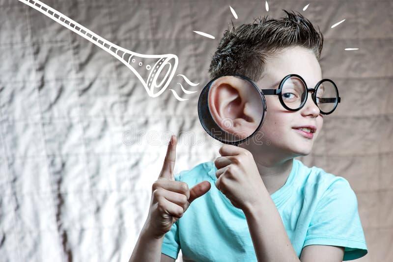 Le garçon dans un T-shirt léger vérifie l'audition par un tube photographie stock libre de droits