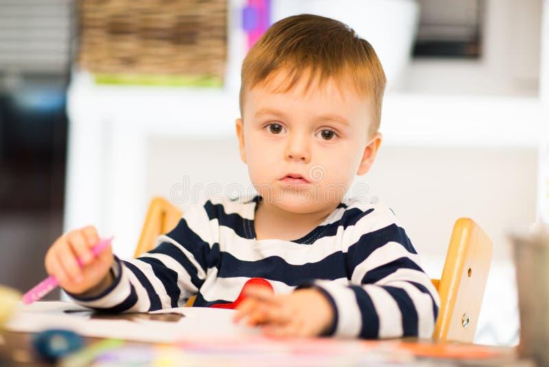 Le garçon dans une chemise rayée dessine et coupe photos libres de droits