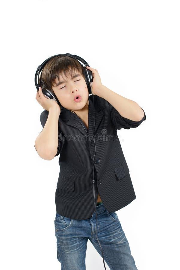 Le garçon darkhaired mignon écoute la musique dans un casque photographie stock