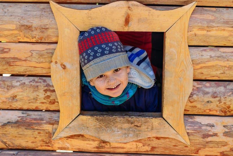Le garçon de cinq ans de sourire de garçon regarde la fenêtre de la maison la maison en bois des enfants sur le terrain de jeu image libre de droits