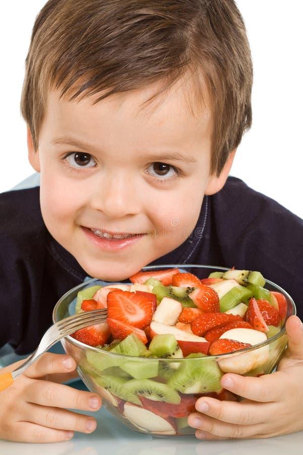 le garçon de cuvette porte des fruits peu sourire découpé en tranches photos stock