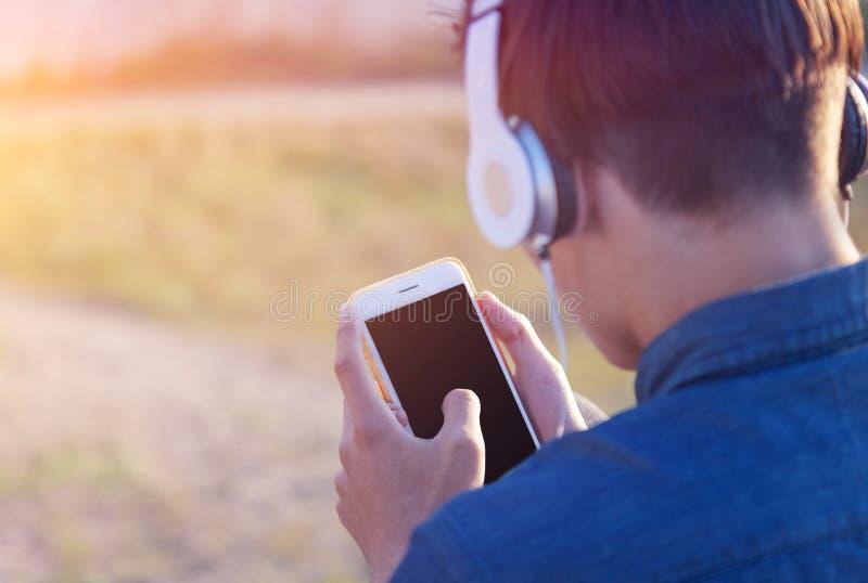 Le garçon de l'adolescence écoute la musique dans des écouteurs dans le téléphone, écran d'isolement noir du téléphone photos libres de droits
