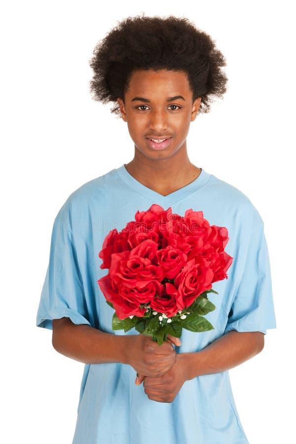 Le garçon de l'adolescence noir donne des fleurs image stock