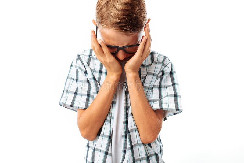 Le garçon de l'adolescence que le renversement essuie ses larmes de main, frustration après école, dans le studio sur un fond bla photo stock