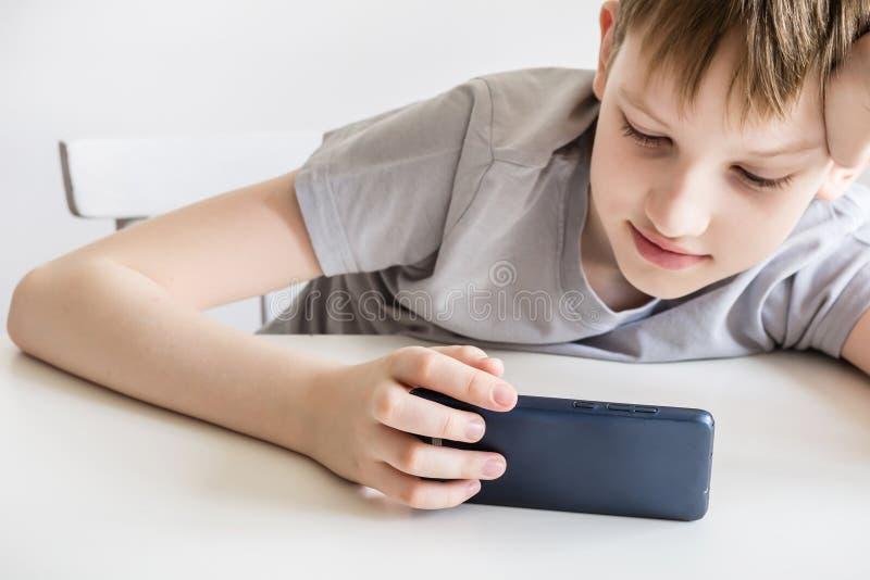 Le garçon de l'adolescence s'assied à la table et au smartphone blancs d'utilisations photos libres de droits