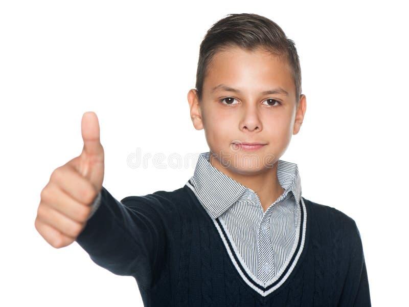 Le garçon de la préadolescence tient son pouce  photo stock