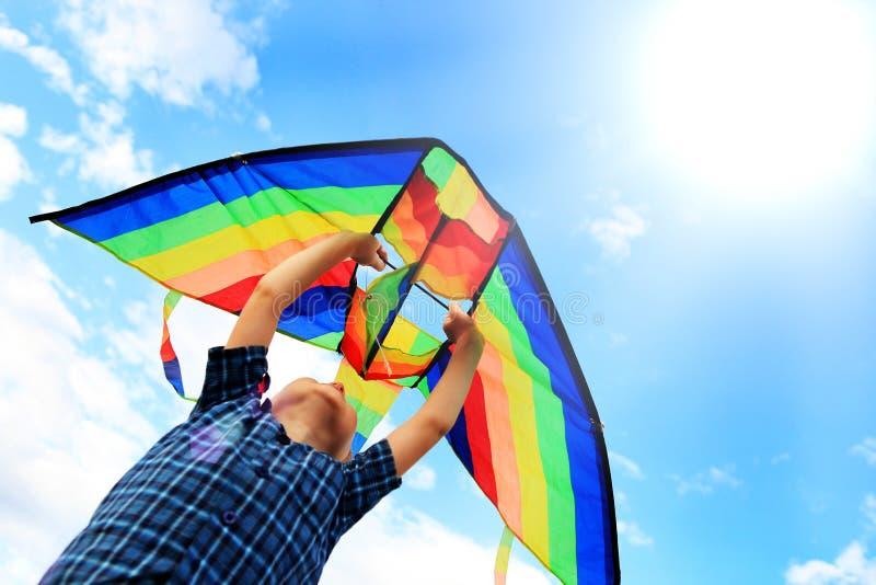 Le garçon de Llittle pilote un cerf-volant dans le ciel image stock