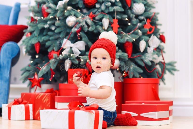 Le garçon de Noël portait des vêtements de fête jouant avec la boîte de cadeaux de Noël Concept des fêtes de Noël et du Nouvel An image libre de droits
