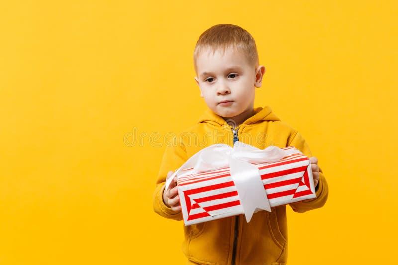 Le garçon de petit enfant 3-4 années portant les vêtements jaunes jugent le boîte-cadeau d'isolement sur le fond orange de mur, s images stock