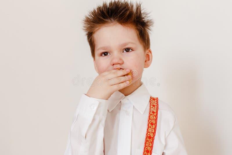 Le garçon de quatre ans russe dans une chemise blanche mange une crêpe sur un fond blanc photos libres de droits