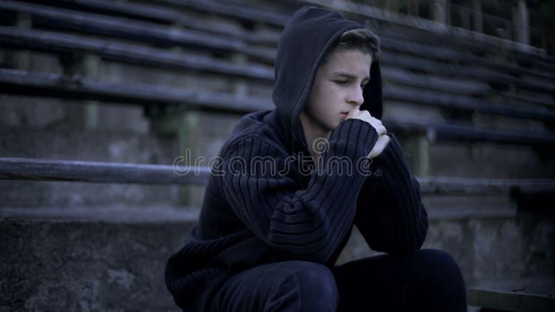 Le garçon de renversement s'asseyant sur la tribune de stade, sent la dépression, la solitude et la peine photos libres de droits