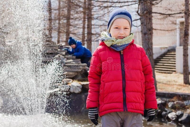 Le garçon de six ans caucasien dans une veste chaude rouge regarde la caméra au printemps images libres de droits