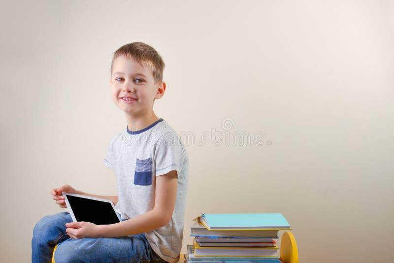 Le garçon de sourire avec la tablette et la pile de livres s'approchent de lui images libres de droits