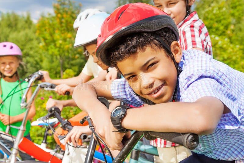 Le garçon de sourire dans le casque tient le guidon du vélo images libres de droits