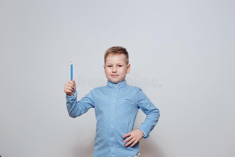Le garçon de sourire dans une chemise bleue avec un crayon sur un fond blanc photo libre de droits