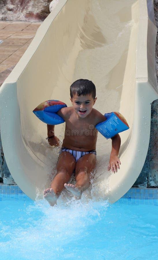 Le garçon de sourire glisse un waterslide images stock