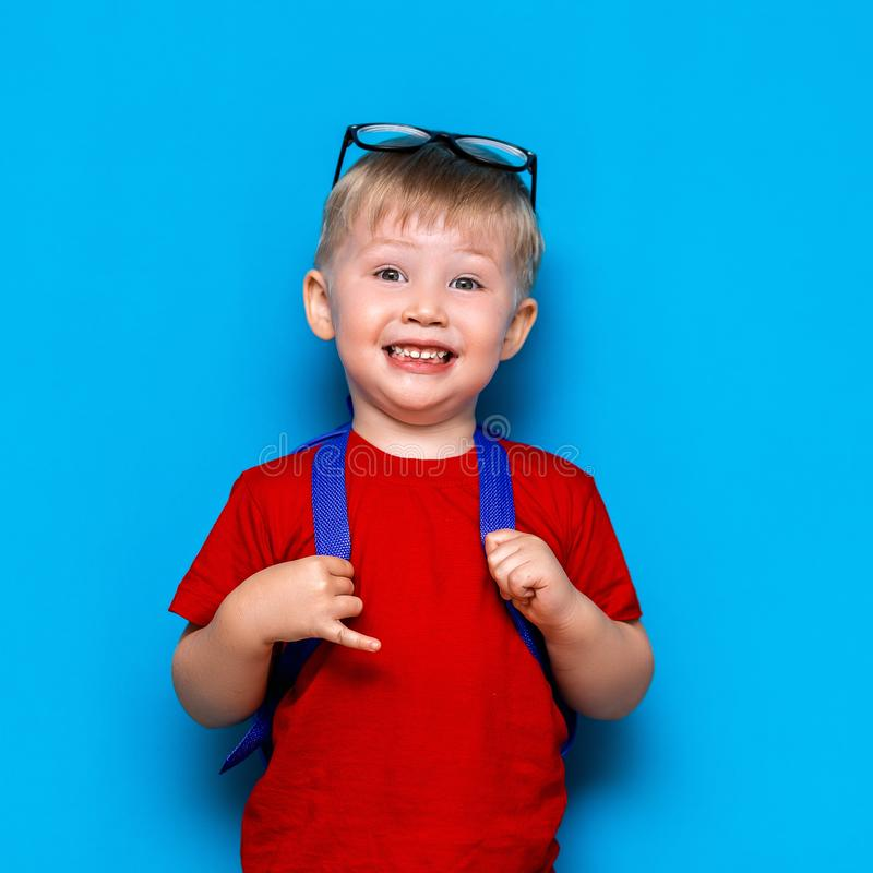 Le garçon de sourire heureux dans le T-shirt rouge avec des verres sur sa tête va instruire pour la première fois Enfant avec le  images libres de droits