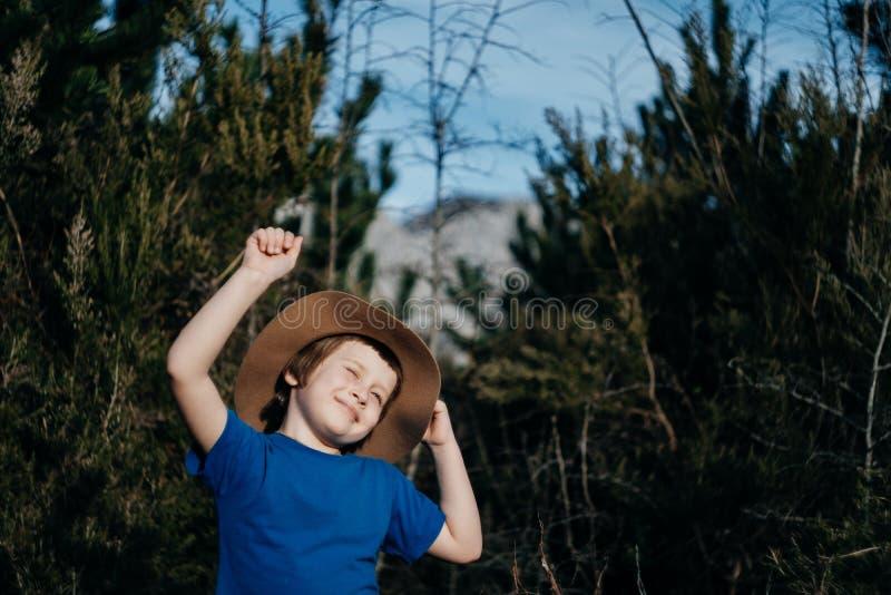 Le garçon de sourire heureux extérieur dans la forêt d'été 6 années badinent dans h photo libre de droits