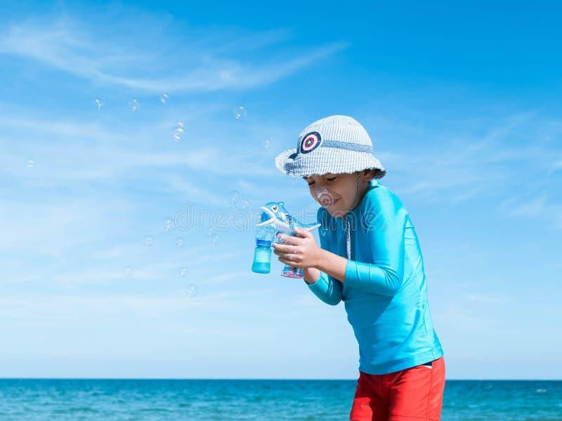 Le garçon de sourire heureux l'Européen dans un T-shirt protecteur bleu et des shorts rouges d'uF sur la plage par la mer bleue c photo libre de droits