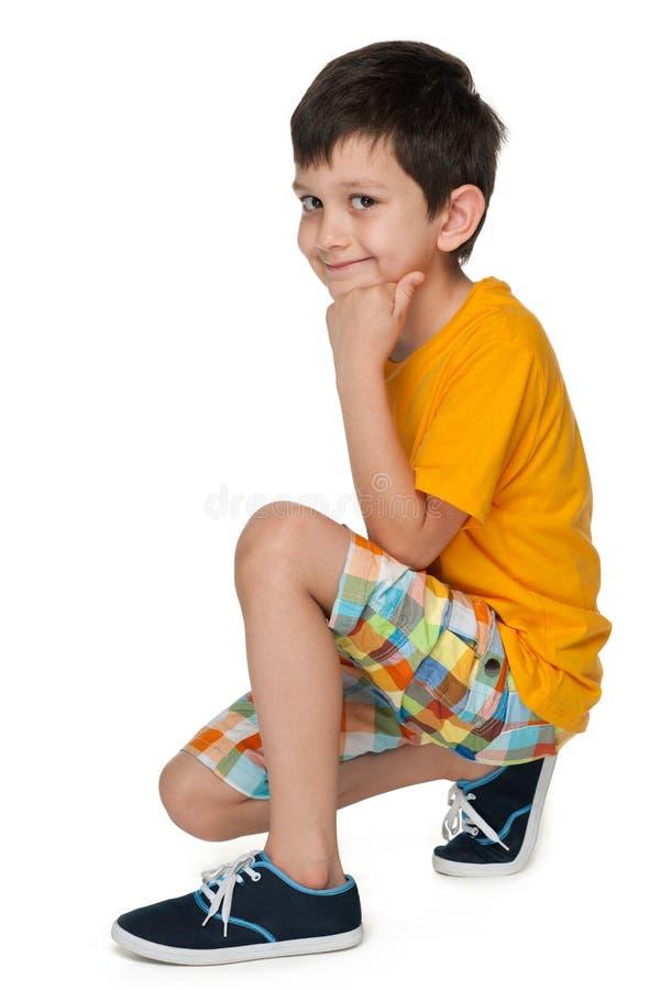 Le garçon de sourire s'assied sur l'étage photographie stock