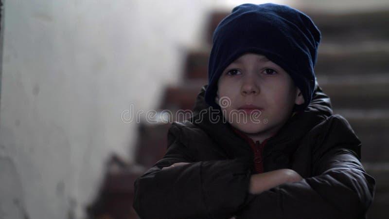 Le garçon de voyou seul s'assied dans un vieux bâtiment délabré, maison de démolition photos stock