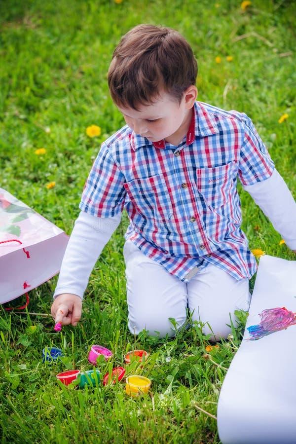 Le garçon dessine sur l'herbe dans le domaine image libre de droits