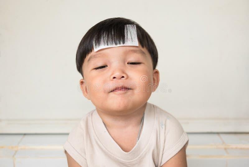 Le garçon dodu adorable smilingly avec cheeked potelé et ferment des yeux Vue de face d'enfant avec la maladie image stock